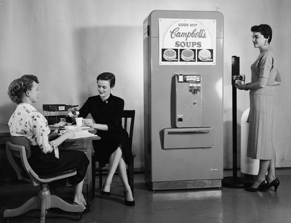 Three women enjoy soup from a Campbell's Soup vending machine in their office, 1950s. One woman opens a can of soup with a fl
