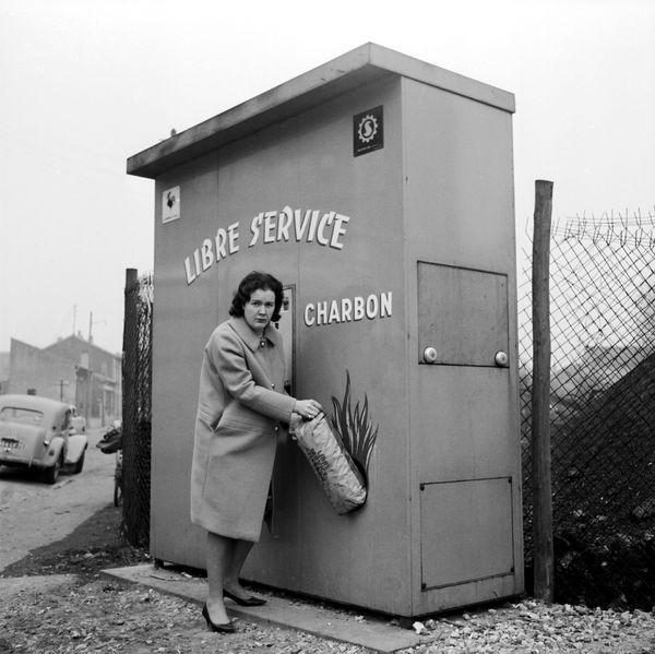 Machine giving out a bag of 5-kilogram balls of coal in the Parisian suburbs, circa 1963.