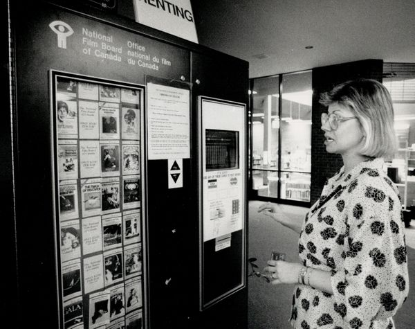 Videotapes for rent from an automatic vending machine, May 10, 1988. Darlene Mathews uses a bank card to select her tape&nbsp