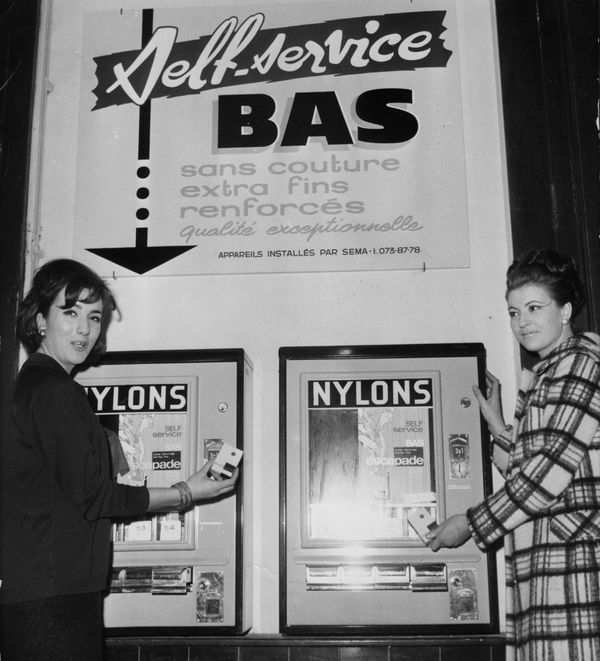 Two women try out the first tights vending machine in Paris, circa 1965.