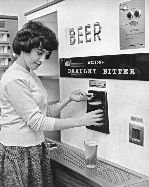 A woman getting a pint of draught bitter from a vending machine, circa 1960s.