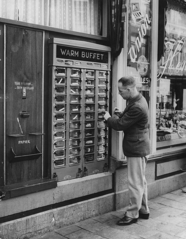 A man buys his warm lunch from a vending machine at Zandvoort in the Netherlands, circa 1950.