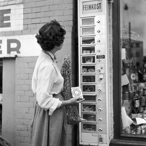 "A woman holds an article which she has just bought from a German ""Feinkost"" vending machine mounted on a shop's wall, circa 1"