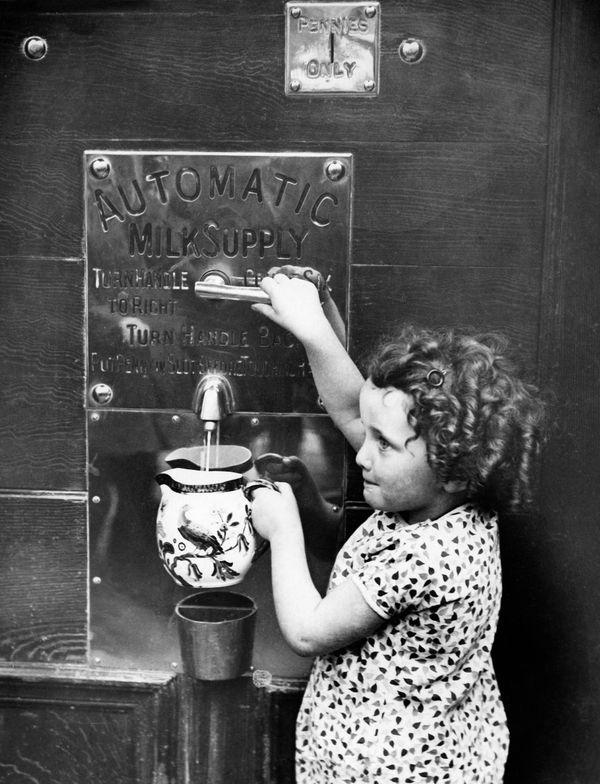 Milk vending machine in London, England, circa 1931.