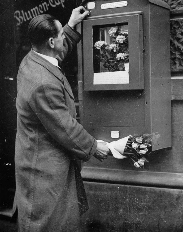 A vending machine for bouquets of flowers in the Western part of Berlin, circa 1930.