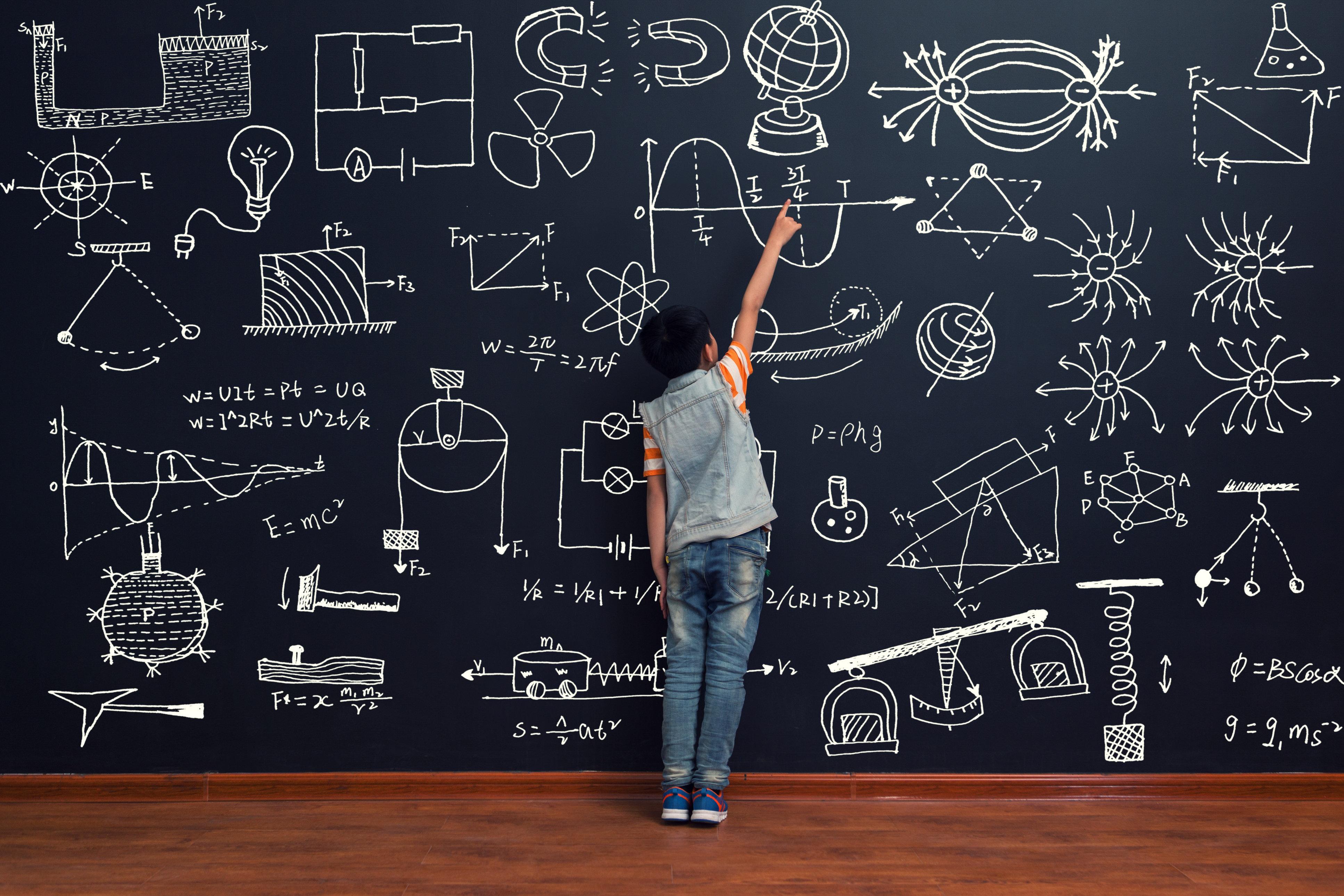 The boy studies in front of the blackboard