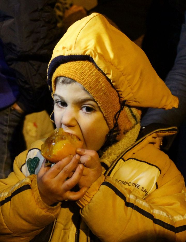 A Syrian child eats a fruit on the outskirts of the besieged rebel-held Syrian town of Madaya, on January 11, 2016, after bei