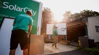 SolarCity Corp. employees unload solar panels from a truck during a home installation in Kendall Park, New Jersey, U.S., on Tuesday, July 28, 2015. SolarCity Corp. is scheduled to release earnings figures on July 29. Photographer: Michael Nagle/Bloomberg via Getty Images