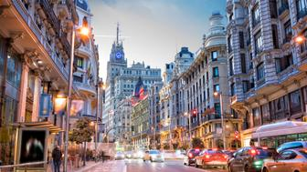 Gran Via of Madrid at sunset with illuminated buildings, and nightlife. Urban landscape in a European capital.