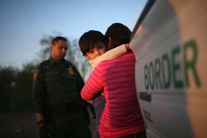 A 1-year-old from El Salvador clings to his mother after she turned themselves in to Border Patrol agents on Dec. 7, 201