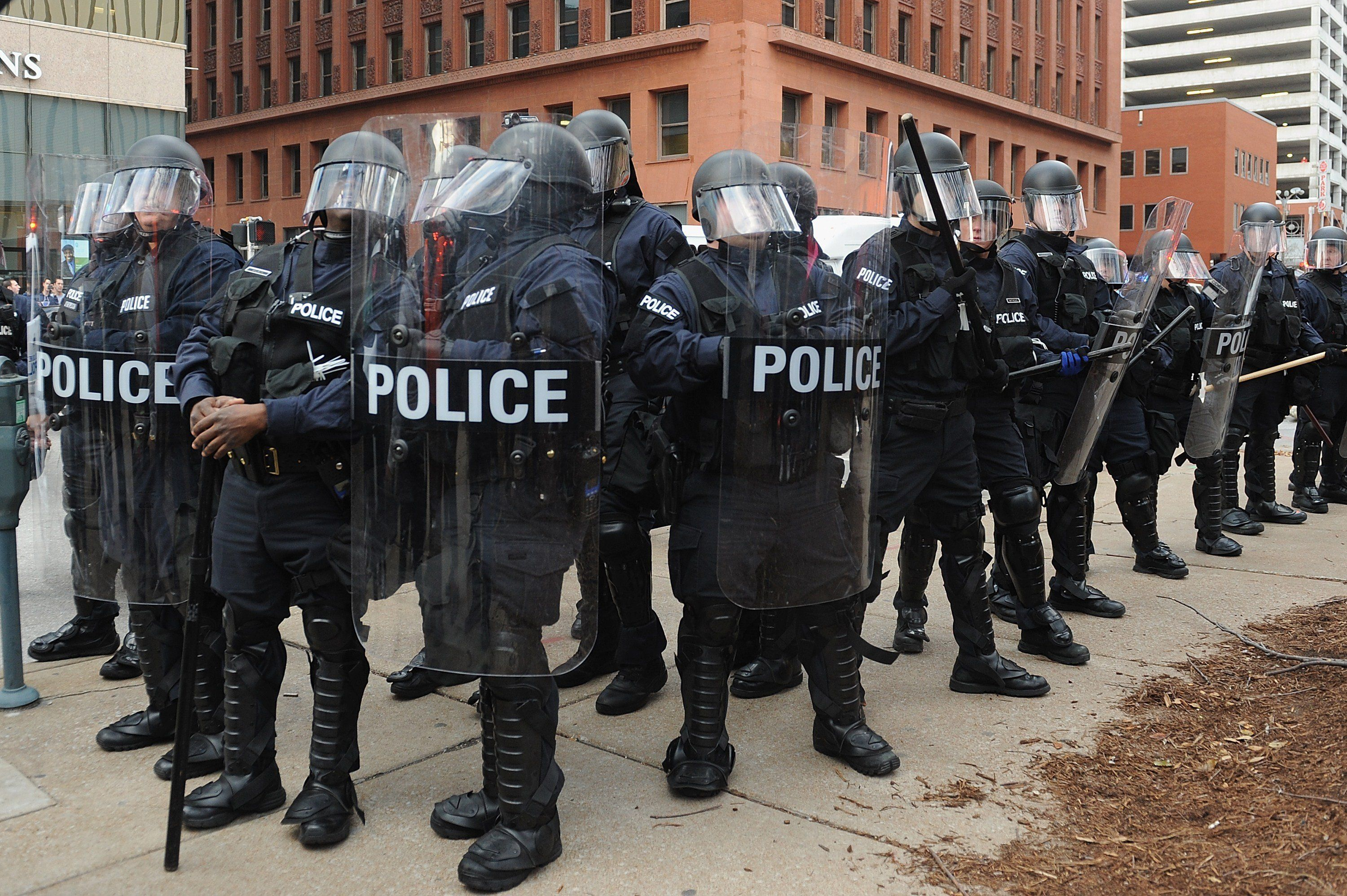 Police officers stand on alert after an arrest was made during a protest in downtown St. Louis, Missouri on November 30, 2014. Demonstrators marched through the streets of St. Louis that eventually led to clashes with police officers and fans from an American Football game between the St. Louis Rams and Oakland Raiders.AFP PHOTO/Michael B. Thomas        (Photo credit should read Michael B. Thomas/AFP/Getty Images)