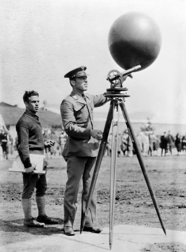 Joseph Danko standing next to aninvention that helps determine the direction of the wind in 1920.