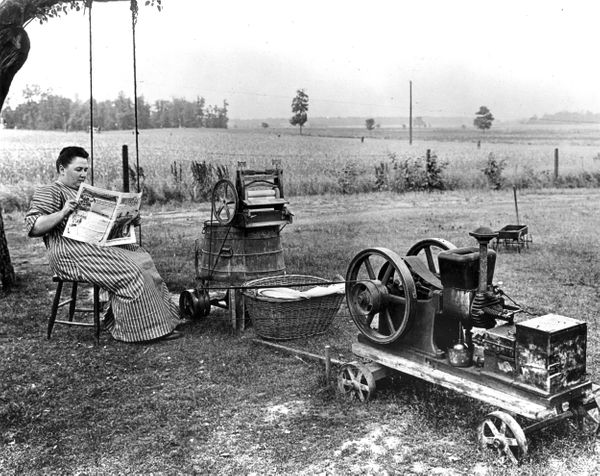 Awoman waiting for her gas-powered washing machine to finish a load of clothing in 1914.