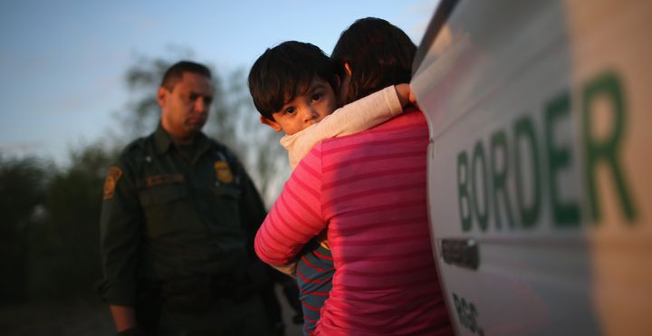 A1-year-old from El Salvador clings to his mother after she turned them in to Border Patrol agents near Rio Grande City