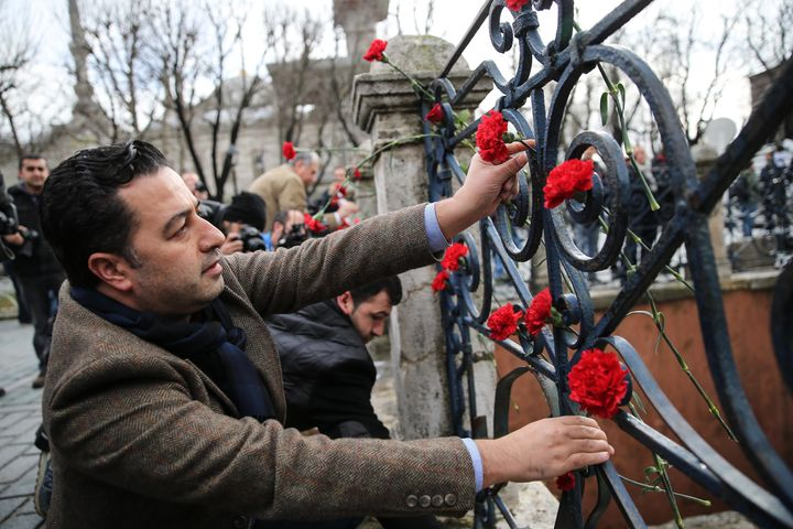 People leave flowers for victims of the attack at Istanbul's Sultanahmet square after it was reopened to the m