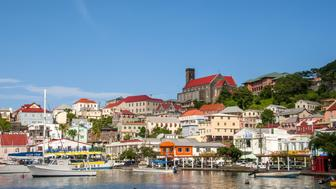 Scenic landscape of the Carenage harbor, boats, and colorful buildings on hillside, St George's, Grenada.