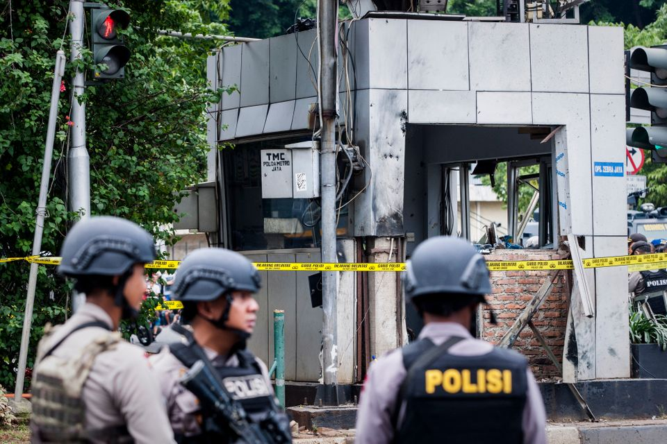 Policemen guard the site of the explosion following the deadly attacks.