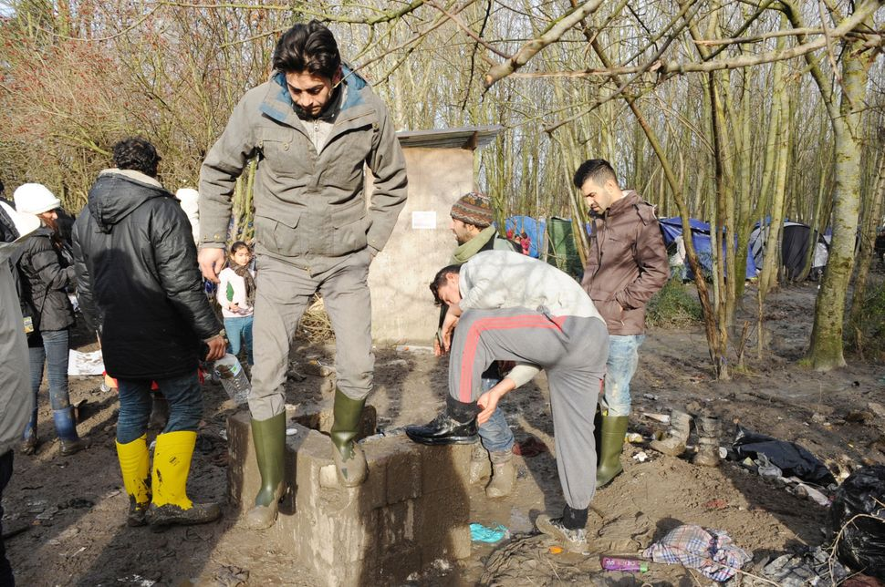 Men gather around the camp's only spigot to wash the mud off of their shoes.