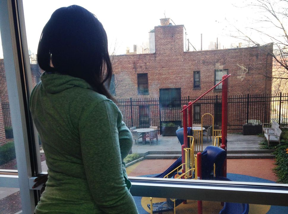 A once-homeless domestic violence survivor looks out the window of her apartment building.
