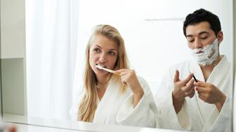 Woman brushing her teeth and man shaving in the bathroom