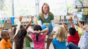 Kindergarten teacher and children with hands raise