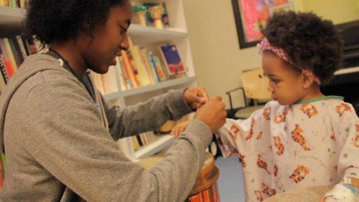 A dancer wraps around the arm of a patient a bracelet they made together.