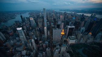 The Manhattan skyline stands at dusk in this aerial photograph taken above New York, U.S., on Friday, June 19, 2015. The Standard & Poor's 500 Index fell, with the gauge dropping below its price for the past 50 days, while Treasuries retreated. Photographer: Craig Warga/Bloomberg via Getty Images