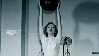 Young woman holding fitness ball in gym