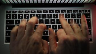 A stream of binary coding, text or computer processor instructions, is seen displayed on a laptop computer screen as a man works to enter data on the computer keyboard in this arranged photograph in London, U.K., on Wednesday, Dec. 23, 2015. The U.K.s biggest banks fear cyber attacks more than regulation, faltering economic growth and other potential risks, and are concerned that a hack could be so catastrophic that it could lead to a state rescue, according to a survey. Photographer: Chris Ratcliffe/Bloomberg via Getty Images
