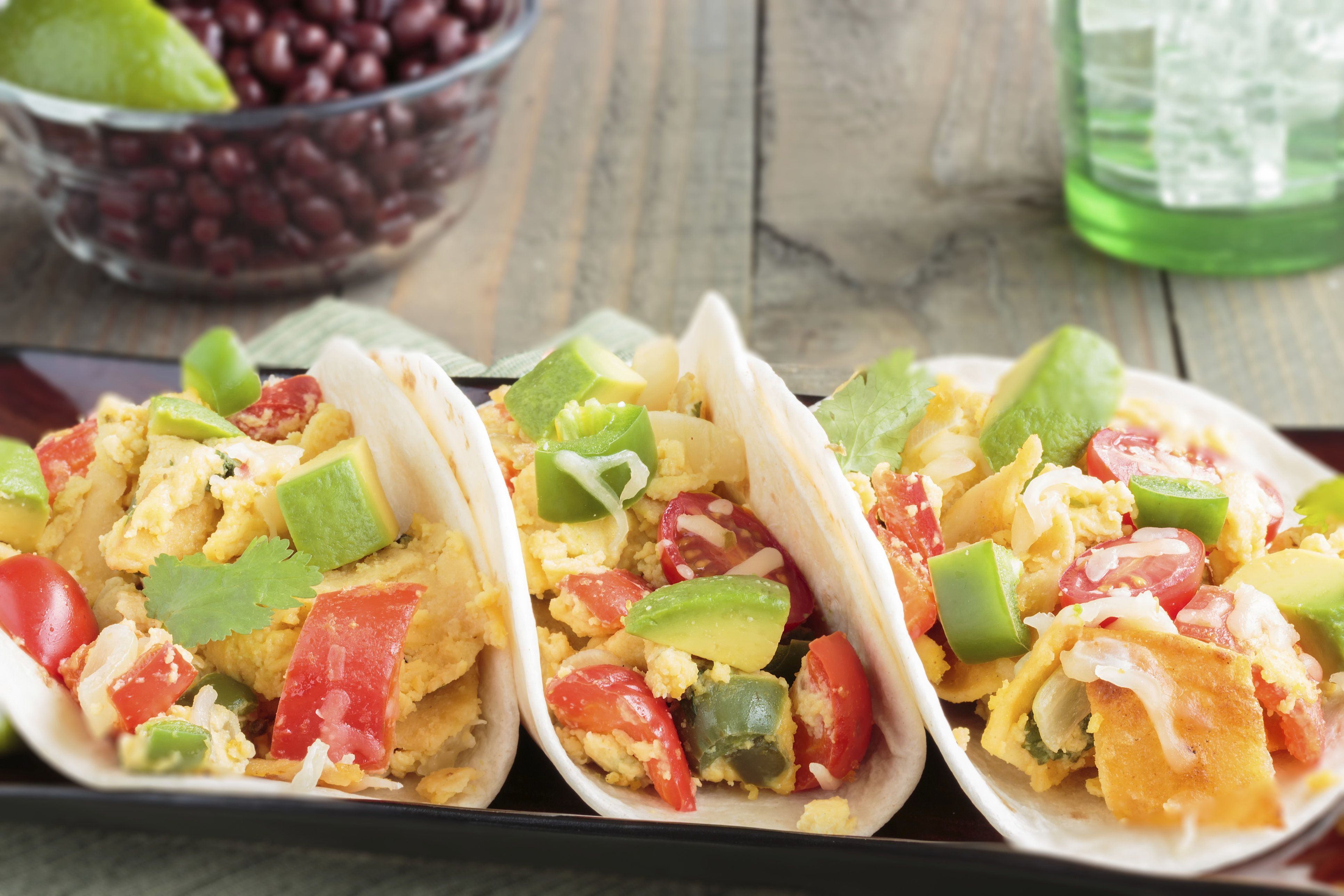 Tacos filled with migas, a Tex-Mex dish of eggs scrambled with red bell pepper, onions, jalapenos, cheese, topped with avocado, cilantro, cherry tomatoes, served with black beans
