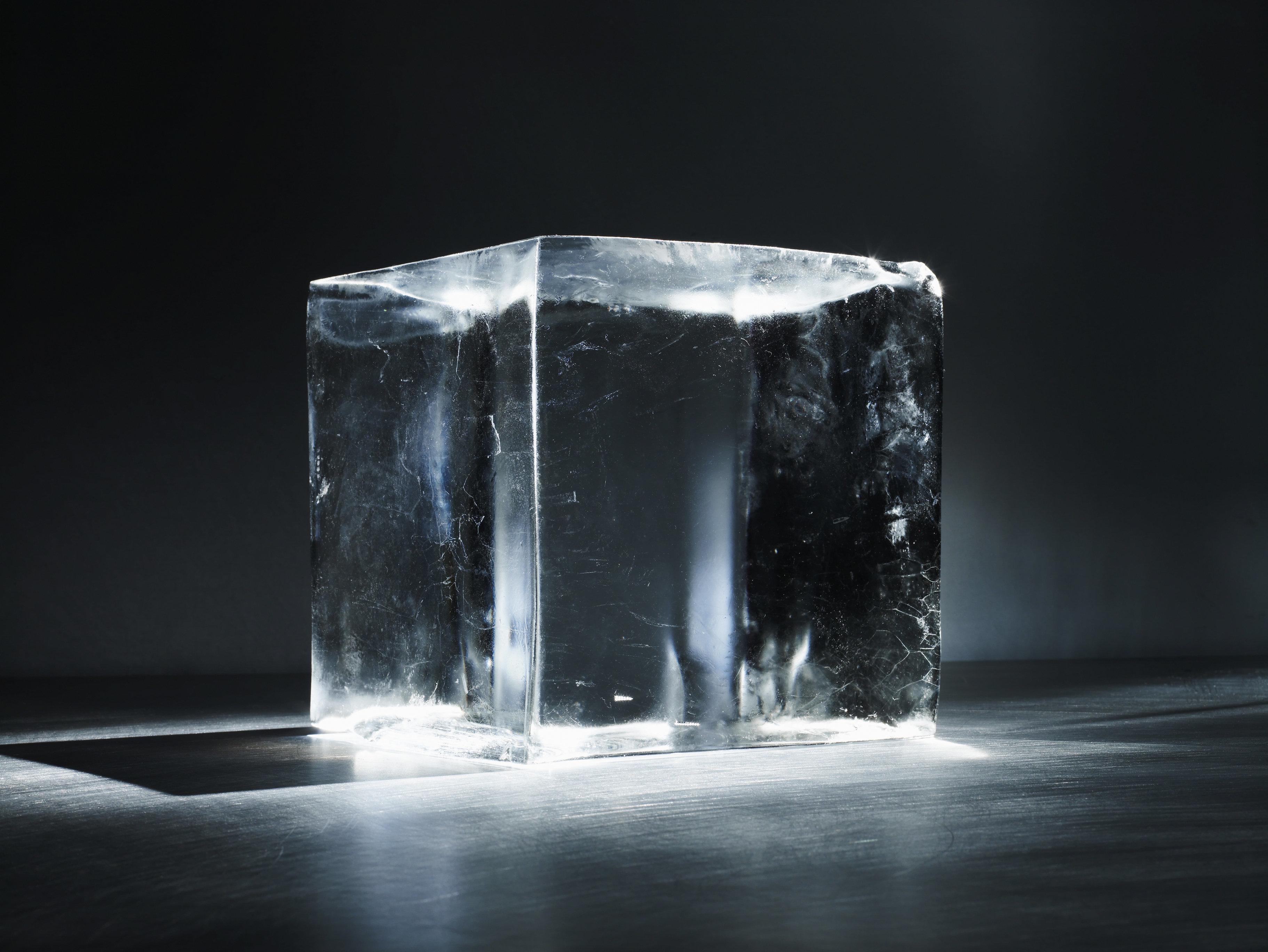 Ice block standing in a dark room.