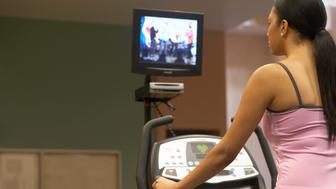 Young woman on treadmill, television in background, rear view