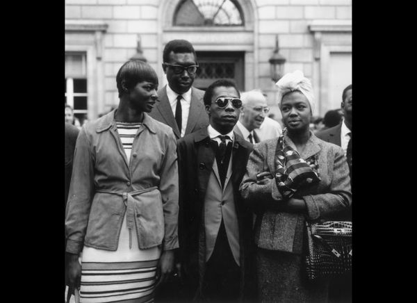 Author and playwright James Baldwin (1924 - 1987), wearing sunglasses, stands between May Mercier (L) and pianist and singer