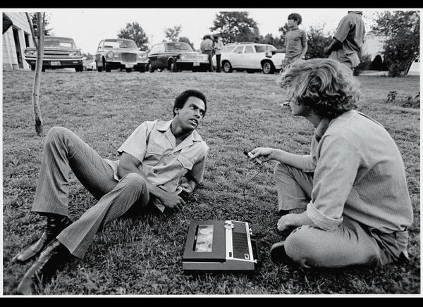 Black Panther Party co-founder Huey P. Newton (1942 - 1989) reclines on the grass as he answers questions from a Liberation N