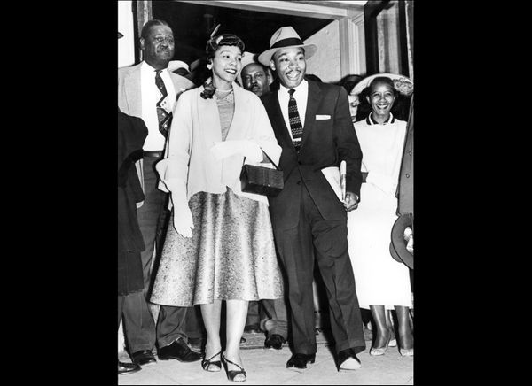 Martin Luther King, 27, and his wife, Coretta Scott King, emerge 23 March 1956 from Montgomery Court House, following his tri