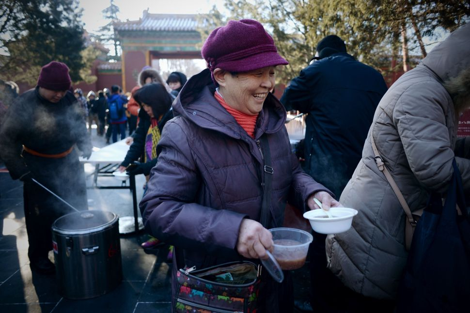 An woman smiles as she receives bowls of Laba congee at the Lama Temple in Beijing.