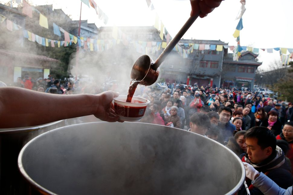 Monks ladle out Laba congee at the Guangren Temple in Xi'an, a city in China's Shaanxi province, on Jan. 17, 2016.