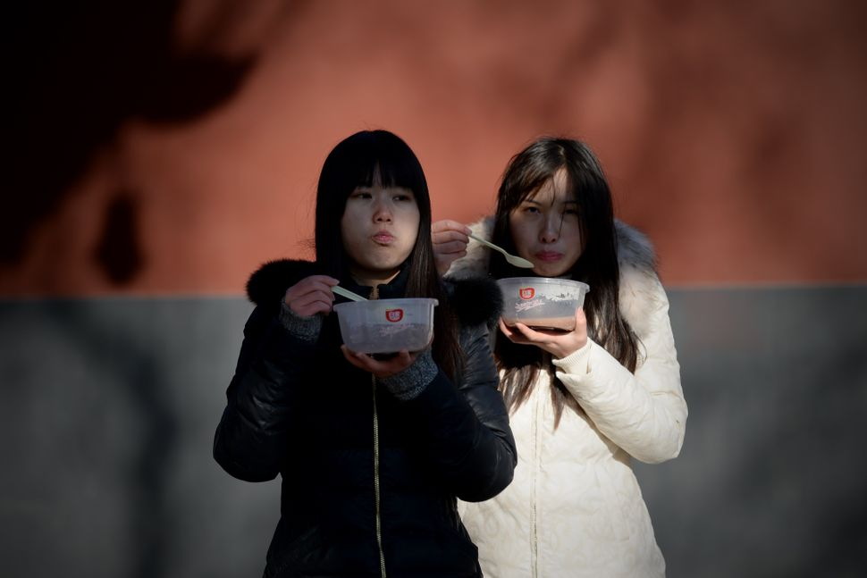 Two women eat Laba congee in Beijing.