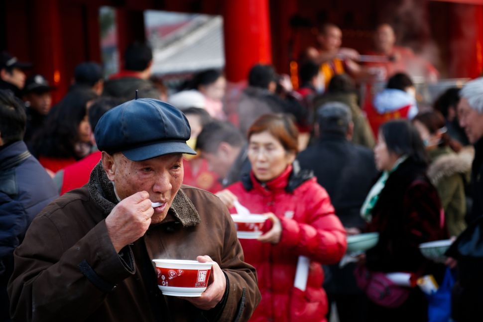 A man eats his Laba congee at Guangren Temple.