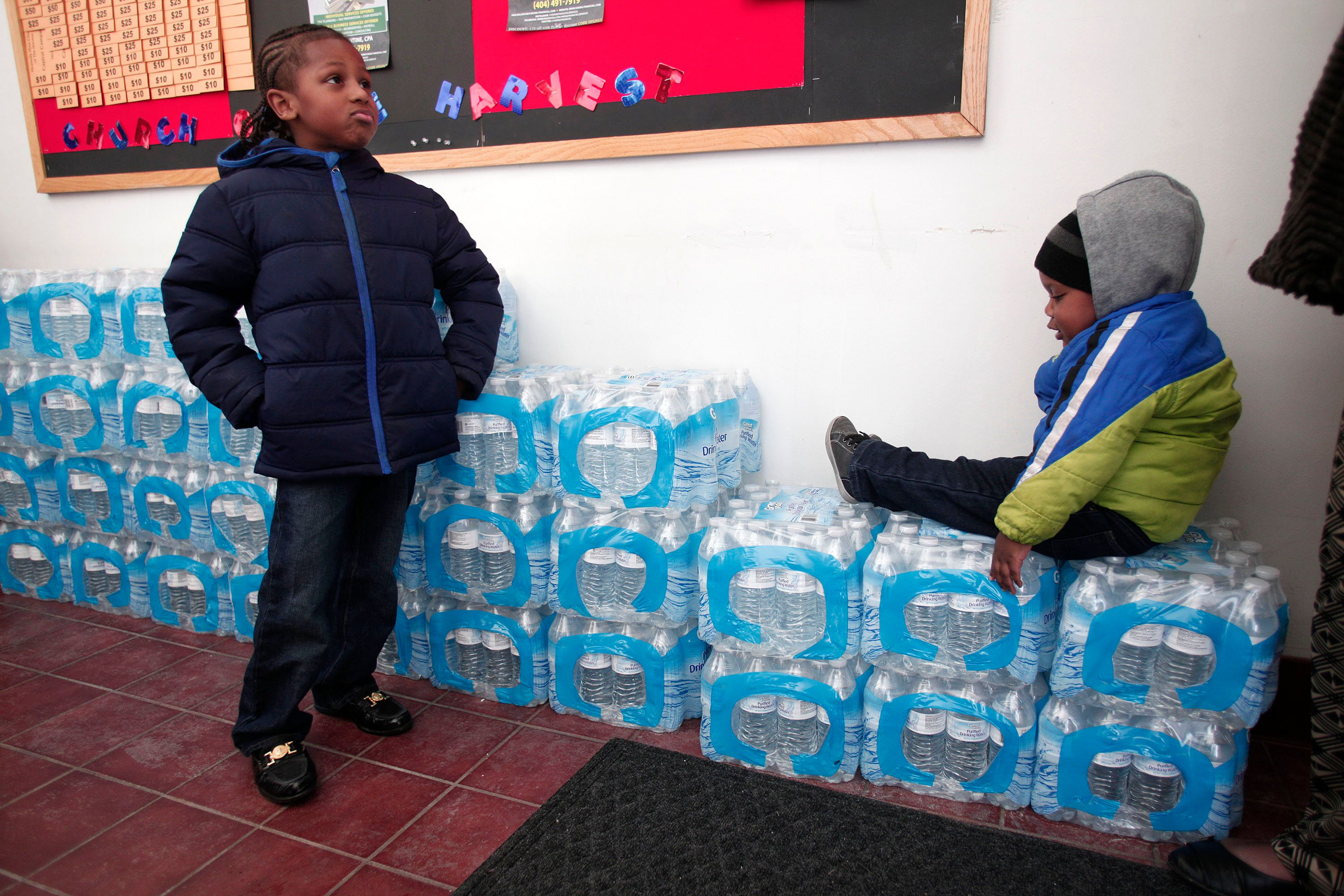Justin Roberson (L), age 6, of Flint, Michigan and Mychal Adams, age 1, of Flint wait on a stack of bottled water at a rally where the Rev. Jesse Jackson was speaking about about the Flint's water crises.
