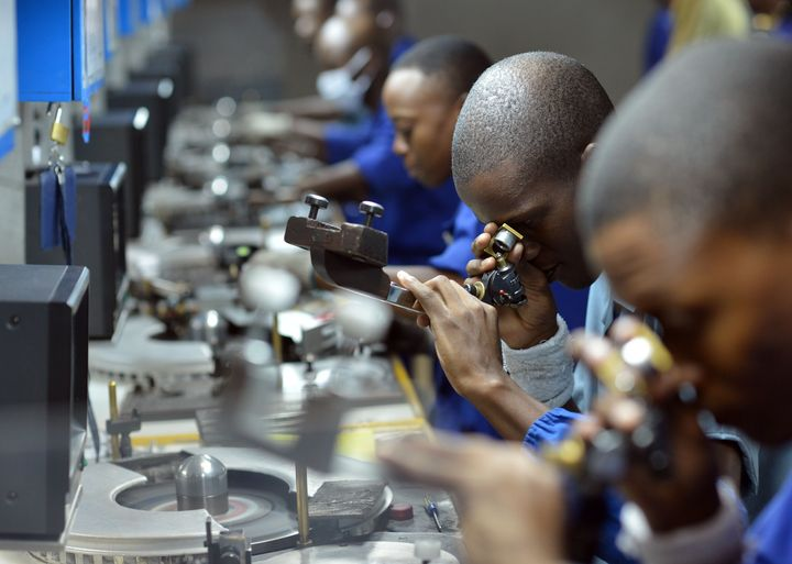 Workers check, cut and polish diamonds at a Diamond cutting and polishing company during the tour by Ghanian President John D