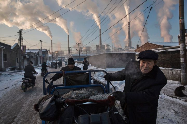 Smoke billows from stacks as Chinese men pull a tricycle in a neighborhood next to a coal fired power plant on November 26, 2