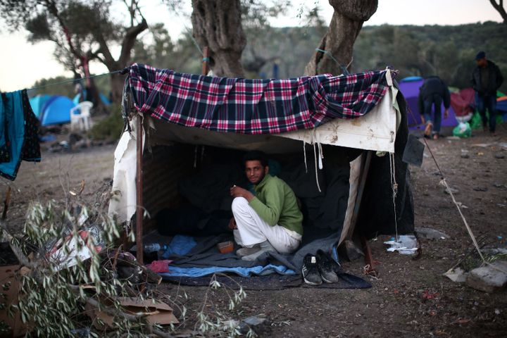 A migrant from Pakistan sits in his makeshift tent on Lesbos, Greece, on Nov. 16, 2015. After arriving on the island, many people sleep in tents with little to no insulation.