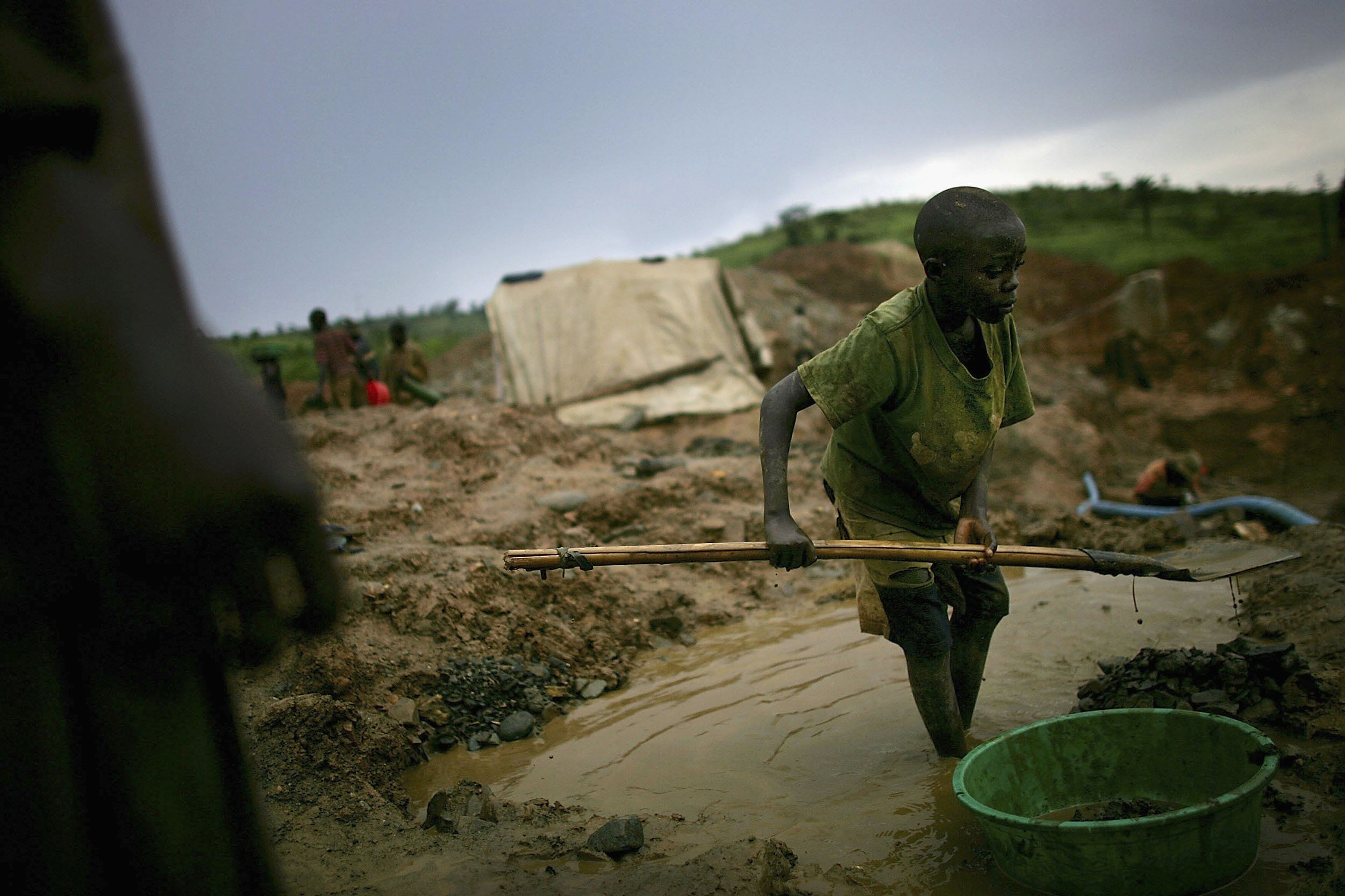MONGBWALU, CONGO - MARCH 27: A boy shovels dirt into a bucket which will be sifted through while looking for gold March 27, 2006 in Mongbwalu, Congo. Thousands of Congolese scrape together meagre livings from mining. Gold and other mineral deposits, which are numerous in the volatile north-east of the country, have become a catalyst to much of the conflict in Congo. The Democratic Republic of Congo (DRC), a country that loses an estimated 1,400 people per day due to war since 1998, is struggling to hold Presidential elections this summer. The volatile East of the country, which is situated hundreds of miles from the capital Kinshasa, has been the focal point of continued violence. Numerous militias and warlords have vied for control of the mineral rich eastern Congo for decades, creating instability and continued bloodshed.  (Photo by Spencer Platt/Getty Images)