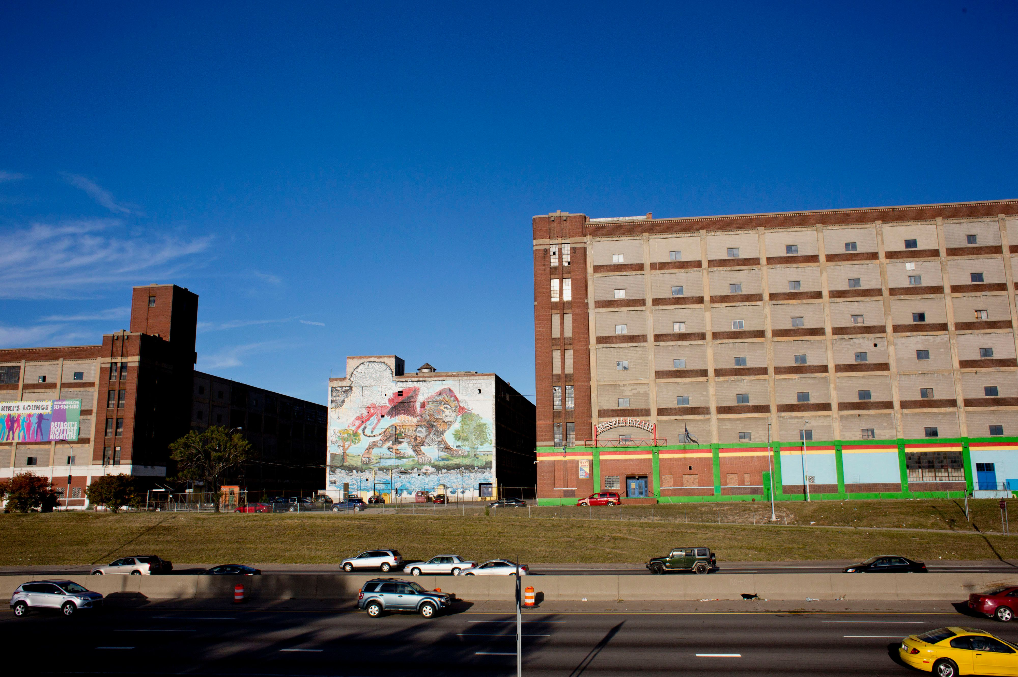 A mural of a lion by artist Kobie Solomon is seen on the side of the Russell Industrial Center as traffic moves along Interstate-75 in Detroit, Michigan, U.S., on Monday, Oct. 5, 2015. Ten months after emerging from a record $18 billion municipal bankruptcy, Detroit is functioning in ways unseen for months and even years -- street lights are on, parks get mowed, municipal debt is sold on the public market and the police are training civilians to manage traffic at clogged intersections. Photographer: Laura McDermott/Bloomberg via Getty Images