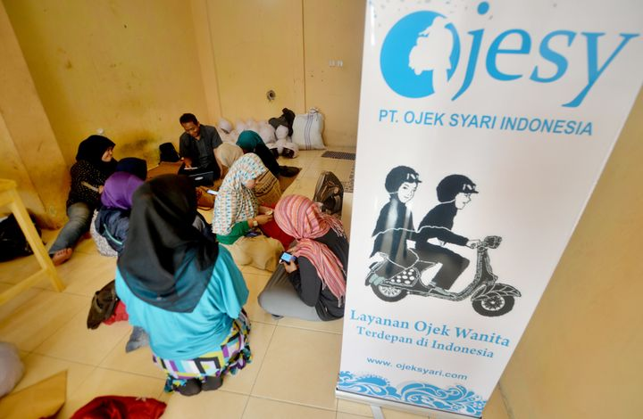 Female motorbike taxi drivers are seen learning how to take orders from their smartphones at an office in Jakarta.