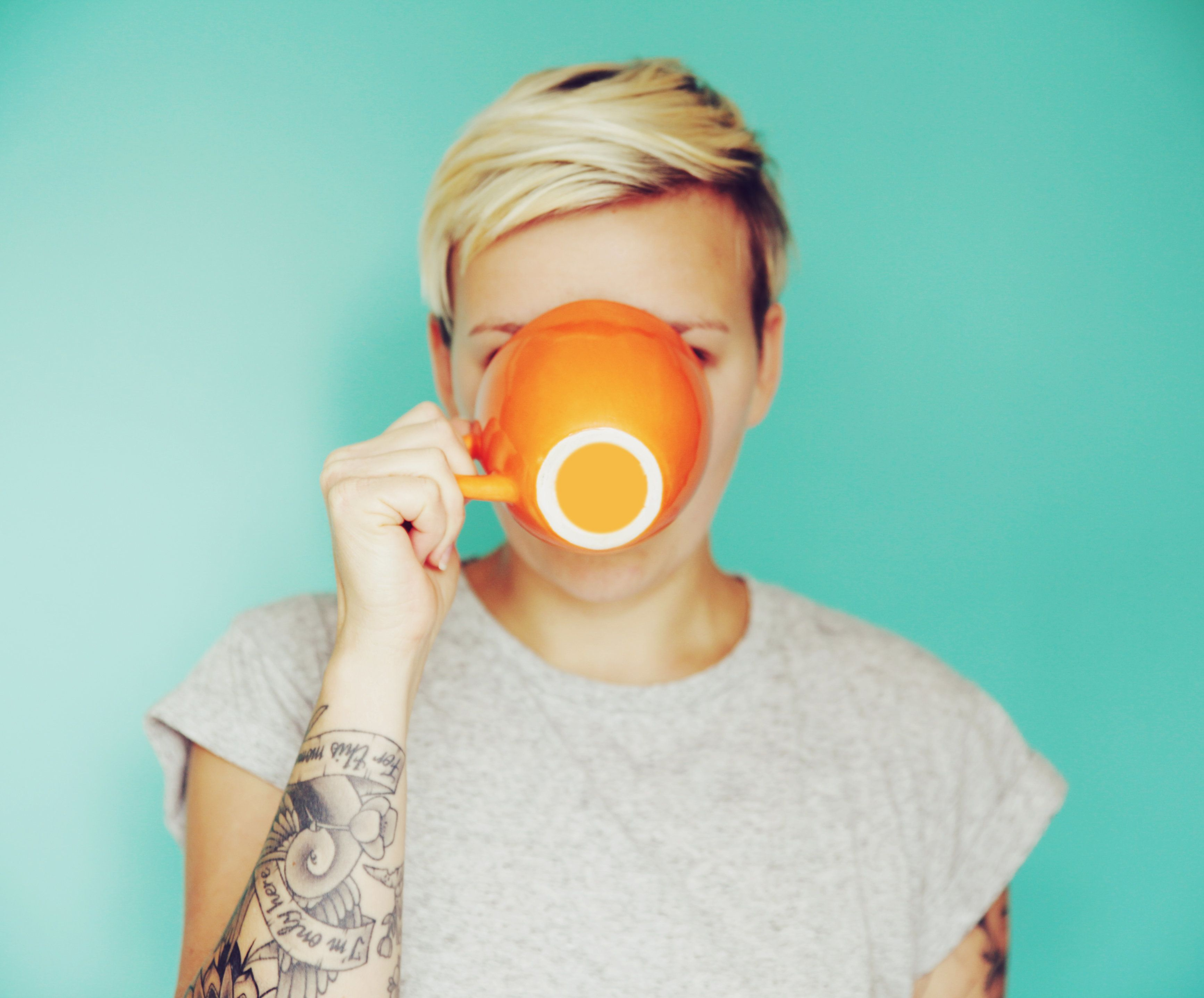 Young woman drinking out of an orange cup on a blue backdrop