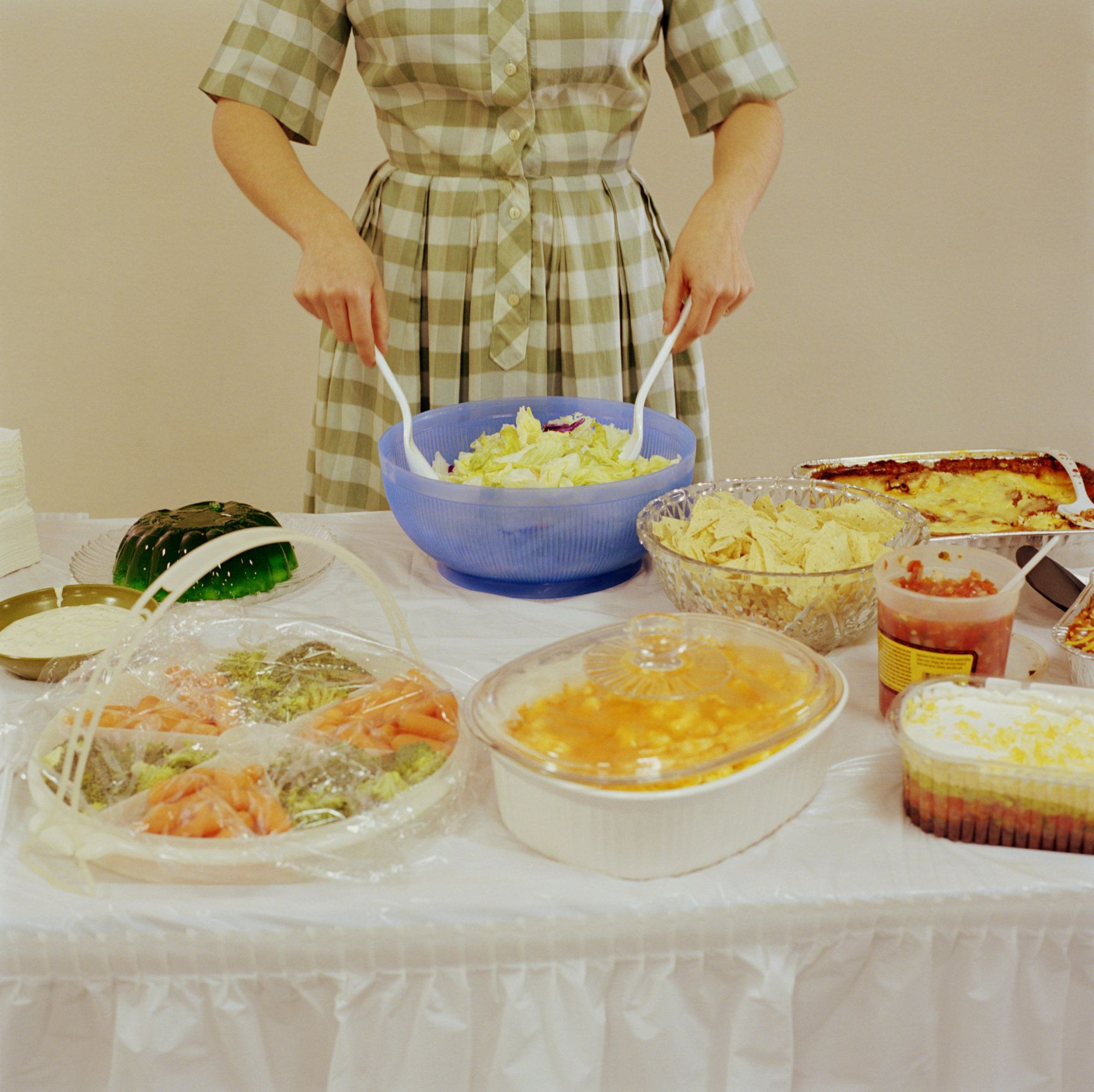 Woman tossing salad in bowl, different foods on table