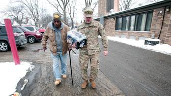 FLINT, MI - JANUARY 13:   Michigan National Guard Staff Sergeant Steve Kiger of Beaverton, Michigan, helps a Flint, Michigan resident  take bottled water out to his car after he received it at a Flint Fire Station January 13, 2016 in Flint, Michigan. On Tuesday, Michigan Gov. Rick Snyder activated the National Guard to help the American Red Cross distribute water to Flint residents to help them deal with the lead contamination that is in the City of Flint's water supply.  (Photo by Bill Pugliano/Getty Images)