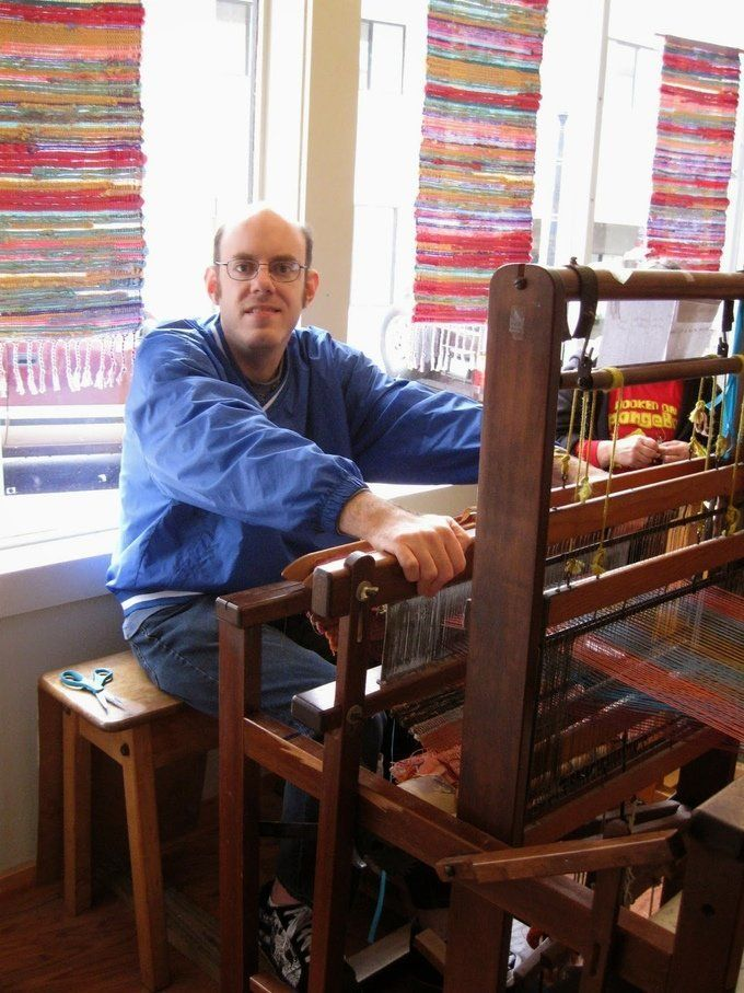 A man looks up from a loom atFlying Shuttles Studio, a Rhode Island nonprofit that supports artists and weavers with in